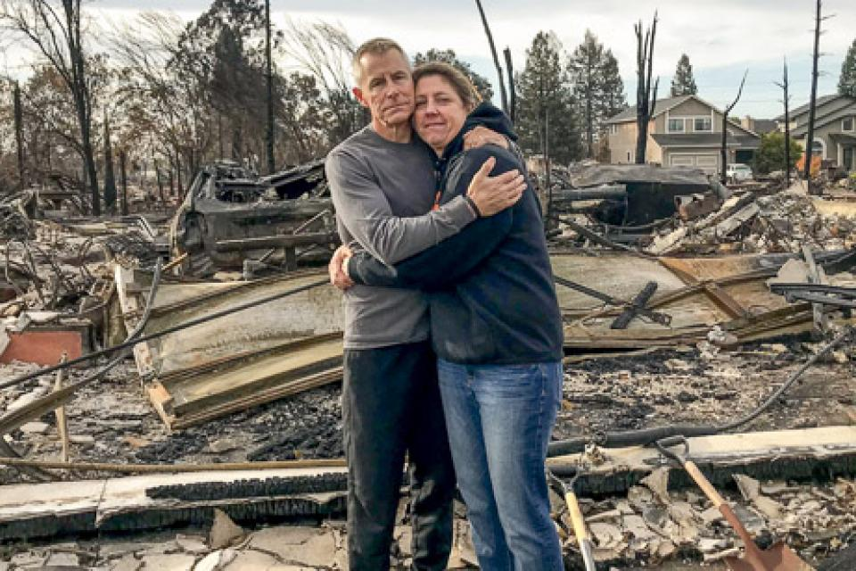 Jen and William Ortlinghaus stand before the wreckage of their home in the wake of the devastating North Bay fires. Both are members of the Petaluma Federation of Teachers.
